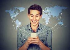La tenuta felice dell'uomo facendo uso dello smartphone ha collegato Internet di lettura rapida Immagine Stock