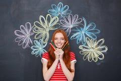 La tenuta felice della donna disegna a matita sopra il fondo della lavagna con i fiori tirati Fotografie Stock Libere da Diritti