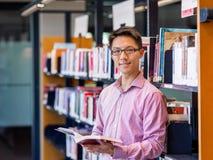 La tenuta felice dello studente maschio prenota alla biblioteca Fotografia Stock Libera da Diritti