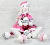 La tenuta femminile del coniglietto di pasqua ha decorato l'uovo Immagine Stock