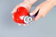 La tenuta femminile di medico della medicina nel cuore rosso del giocattolo delle mani e lo stetoscopio si dirigono Cardio therap Immagine Stock