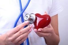 La tenuta femminile di medico della medicina nel cuore rosso del giocattolo delle mani e lo stetoscopio si dirigono Cardio therap Immagine Stock Libera da Diritti
