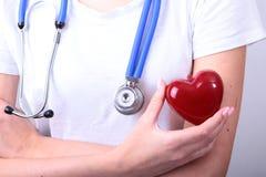 La tenuta femminile di medico della medicina nel cuore rosso del giocattolo delle mani e lo stetoscopio si dirigono Cardio therap Fotografia Stock