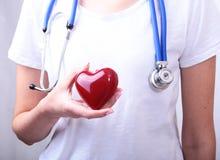La tenuta femminile di medico della medicina nel cuore rosso del giocattolo delle mani e lo stetoscopio si dirigono Cardio therap Immagini Stock