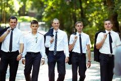 La tenuta fiera della passeggiata dei groomsmen e dello sposo i loro rivestimenti più dovrebbe immagini stock