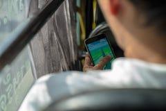 La tenuta non identificata dell'uomo un telefono mentre gioca Pokemon va in sua mano in autobus Fotografia Stock