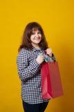 La tenuta più di taglia felice della donna ha colorato i sacchetti della spesa sopra fondo giallo Immagine Stock
