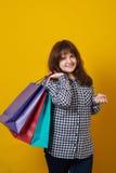 La tenuta più di taglia felice della donna ha colorato i sacchetti della spesa sopra giallo Fotografia Stock