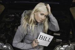La tenuta preoccupata della donna firma dentro il garage Fotografia Stock Libera da Diritti