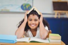 La tenuta sorridente dell'allievo prenota sulla testa in un'aula Immagine Stock Libera da Diritti