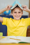 La tenuta sorridente dell'allievo prenota sulla testa in un'aula Fotografia Stock Libera da Diritti