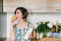 La tenuta sorridente della donna impanano ed il ritratto della bottiglia per il latte sulla cucina Fotografia Stock
