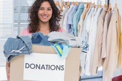 La tenuta volontaria copre la scatola di donazione immagini stock
