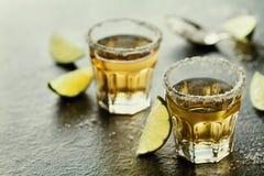 La tequila ha sparato con calce e sale marino sulla tavola nera Immagine Stock Libera da Diritti