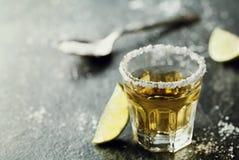 La tequila ha sparato con calce e sale marino sulla tavola nera Fotografia Stock