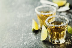 La tequila a tiré avec la chaux et le sel de mer sur la table noire photographie stock libre de droits