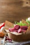 La ternera cruda cortó en pedazos con las verduras y otros ingredientes Imagenes de archivo