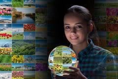 La terra della tenuta della giovane donna con le foto della natura Immagini Stock