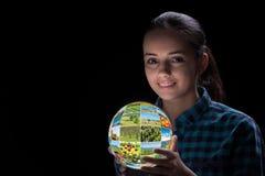 La terra della tenuta della giovane donna con le foto della natura Fotografia Stock Libera da Diritti