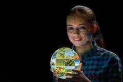 La terra della tenuta della giovane donna con le foto della natura Fotografia Stock