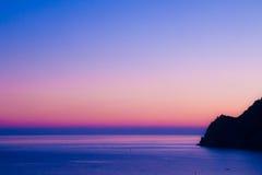 La terra incontra il mare al tramonto fotografia stock