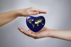 La terra sotto forma di cuore in mani Immagini Stock