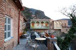 La terraza al aire libre con las tablas Casas residenciales en la ladera en Tbilisi vieja Fotos de archivo
