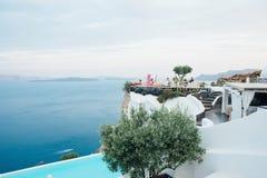 La terraza hermosa con las sillas rosadas, la gente y el mar ven la isla Grecia del santorini Fotografía de archivo