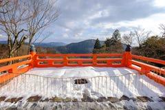 La terraza roja de madera en invierno Imágenes de archivo libres de regalías