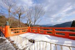 La terraza roja de madera en nieve del invierno Foto de archivo