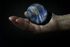 la terre 3d sur la main dans l'obscurité Image libre de droits