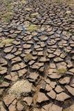 La terre criquée avec de l'eau d'un barrage vide photographie stock libre de droits