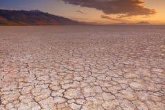 La terre criquée dans le désert à distance d'Alvord, Orégon, Etats-Unis au lever de soleil Images libres de droits