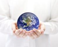 La terre dans des mains Photo stock