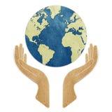 La terre dans des mains a réutilisé le métier de papier Image libre de droits