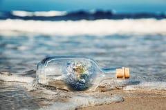 La terre dans la bouteille venant avec la vague de l'océan Environnement, message propre du monde Photos libres de droits