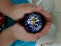 La terre dans le backgorund de mains? produit en picoseconde? Images stock
