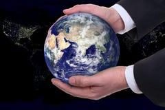 La terre dans mains, ville de nuit Photo libre de droits