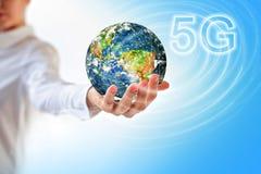 La terre de l'espace dans des mains, globe dans des mains concept sans fil mobile d'Internet de 5G k Éléments de cette image meub Photos libres de droits