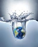 La terre de planète, éclaboussant dans l'eau Images libres de droits