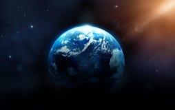 La terre de planète avec le soleil se levant de l'espace lointain Photographie stock libre de droits