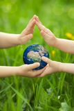 La terre de planète chez des mains du ` s des enfants Photo stock
