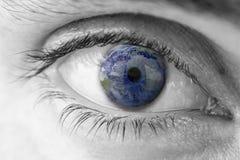 La terre de planète dans l'oeil humain Photographie stock