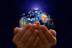La terre de planète dans les mains d'un enfant Photo libre de droits