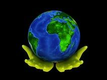 La terre de planète sur des paumes Images stock