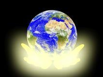 La terre de planète sur le fond de paumes. Photos libres de droits