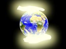 La terre de planète sur le fond de paumes. Photos stock