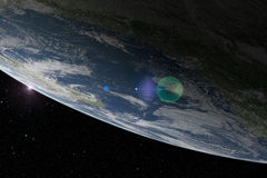 La terre de planète de ci-dessus avec la fusée de lentille Photo libre de droits