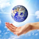 La terre de planète et main humaine Images stock
