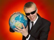 La terre de prise d'homme d'affaires Image stock